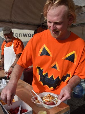 J.J. Haring prepares a Door County caramel apple — sliced apples, caramel, whipped topping, candy sprinkles, nuts, topped with a cherry —at a previous Pumpkin Patch in Egg Harbor. This year's community-wide fall festival takes place Oct. 7-8.