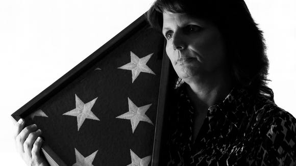 Lynn Campos holds the flag given to her at the funeral of her father, Bill Pisula in her home in Mesa, AZ on Friday, June 6, 2014. Pisula, a veteran, passed away waiting nearly five months for a doctor's appointment at the VA.