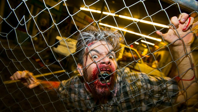 A frightener snarls at visitors in Zombieland at the 13th Floor Haunted House.