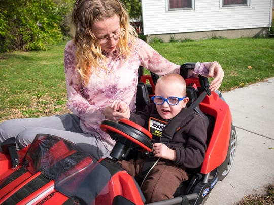 Kathryn Vancamp helps her son, Isaac, 4, in his customized