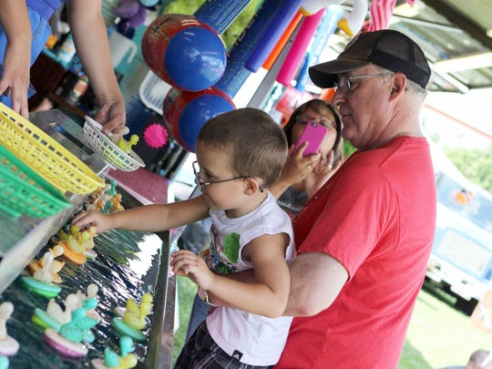 Gary Zastrow of Watertown helps his grandson Brayden Schwark of Middleton in the pick-a-duck game at a past Derby Days, while grandma Laura Zastrow captures the moment.