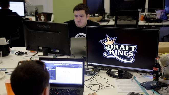 In this file photo, Len Don Diego, marketing manager for content at DraftKings, a daily fantasy sports company, works at his station at the company's offices in Boston.