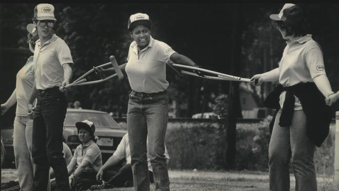 Tammy McCrary (left) is one of thousands of Wisconsin participants in Hands Across America who traveled to Gilman, Ill., for the event on May 25, 1986. She sprained her ankle three days earlier but used her crutches to extend her reach. The line snaked unbroken along U.S. Highway 45 for three miles through the Gilman area.
