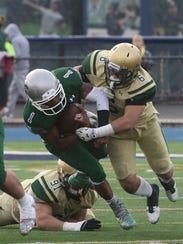 DePaul quarterback Taquan Roberson is tackled by Evan
