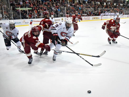 Players chase a loose puck near the Denver goal during