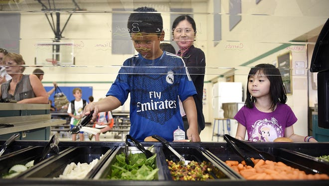 Pine Meadow Elementary School fourth-grader Ryan Quach, 9, shows his sister Alyson, 5, who is going into kindergarten, how the school lunch line works while their mom, Bess, watches during an open house Wednesday in Sartell.