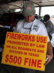 Russell Nettles owner of Russell's Fireworks Kingdom displays one of several signs that he had made to make the public aware of a Texas law that prohibits the use of fireworks along roadways and ditches. Nettles provided the county with many signs to display along roads to urge people to use fireworks responsibly.