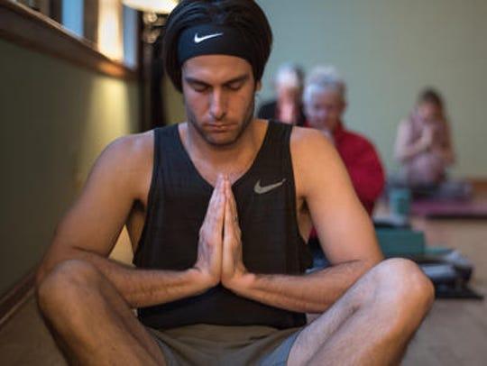 Mike Craparo, Marlboro, meditates during the class.