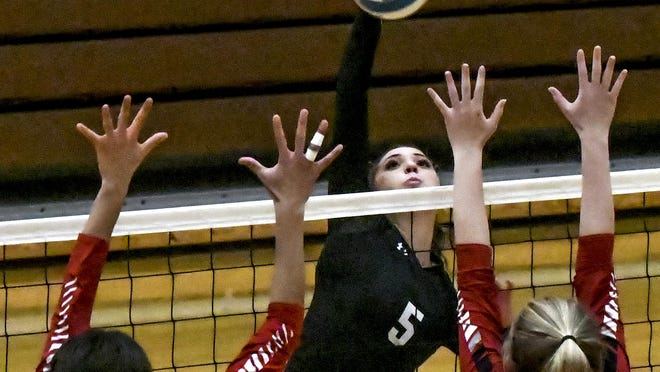 Garden City High School's Julie Calzonetti, center, drives a kill between a pair of Great Bend defenders for a point earlier this season at GCHS. GCHS won a regional volleybal title Saturday at Dodge City and will play in the state tournament Friday.