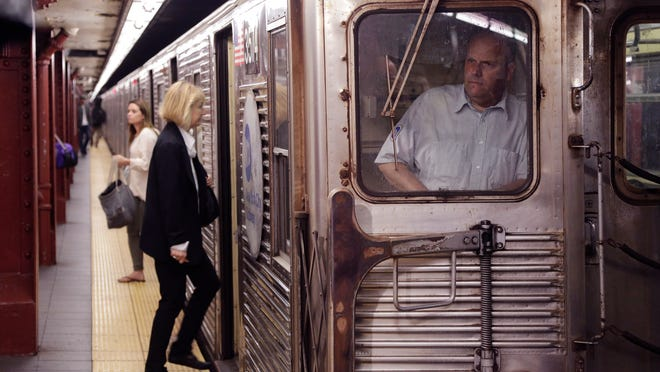"""A subway motorman watches from his cab as passengers enter a train, Thursday, Sept. 25, 2014 in New York. New York Governor Andrew Cuomo says the state is acting with """"the utmost precaution"""" following a report of a possible plot against U.S. subway systems. Iraq's prime minister said Thursday that captive militants had told his country's intelligence agents about an alleged plot targeting subway systems in the U.S. and Paris."""