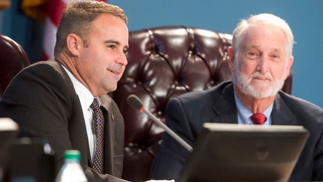 Escambia County Commissioner Doug Underhill, left, takes his place on the board next to Wilson Robertson, right, during a special installation and organization meeting of the commission Nov. 18, 2014.