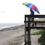 A man named Carter shields himself from the rain with a beach umbrella as he feeds the seagulls Friday afternoon on Hightower Beach in Satellite Beach.