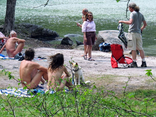People relax at the clothing-optional beach known as the Southwest Cove of Lake Willoughby in Westmore, May 18, 2017.
