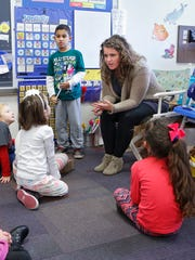 With the assistance of student Victor Martinez, kindergarten teacher Claire Brown reviews the calendar with class Wednesday, January 25, 2017, at Mayflower Mill Elementary.