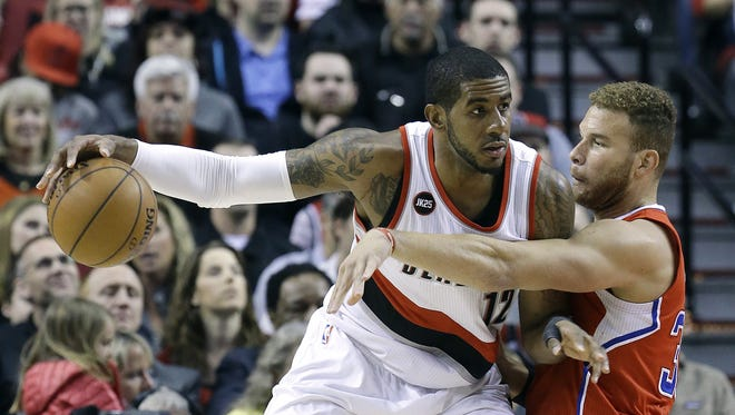 Portland Trail Blazers forward LaMarcus Aldridge, left, works the ball in against Los Angeles Clippers forward Blake Griffin during the first half of an NBA basketball game in Portland, Ore., Wednesday, April 1, 2015.
