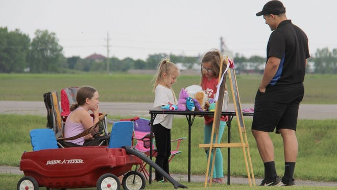 Domino's Pizza delivery driver Austin Steele stops for a cup of lemonade Thursday afternoon at the stand run by Gianna Lubarski, left, and sisters Hattie and Ruby Larson.