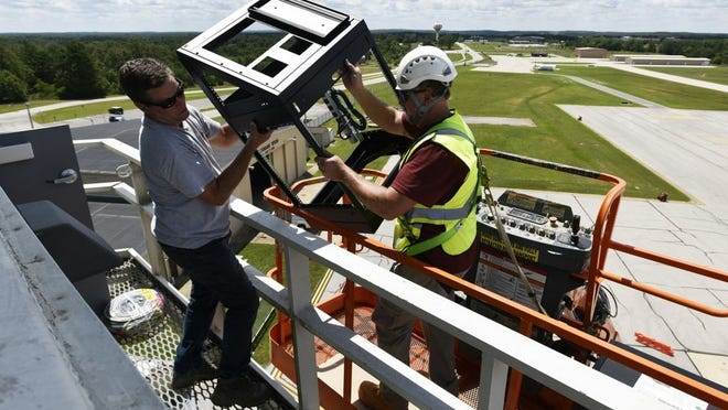 Contractors Paul Harrison (left) and Chris LaCoste bring custom-built computer console equipment to the seventh floor of Forney Airfield's air traffic control tower Aug. 5. The tower upgrades are set to be completed by Oct. 1.