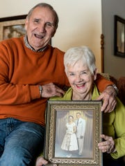 Tom and Pat Keefer hold their wedding photo as they pose for a photo inside their Jonestown home on Monday, Feb. 1, 2016.