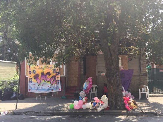 A memorial grows Monday outside the scene of a house