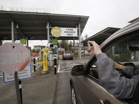 A driver holds up a NEXUS identification card at a border crossing from Canada into the United States,.