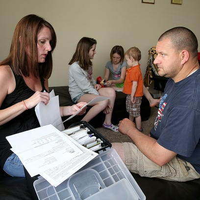 Jenny and Chris Nugent look through the files of paper work from test results from their former home that they found out was contaminated from a methamphetamine lab by the previous owner. Their children Jaylin, left, Mason and Kaily play in the background.