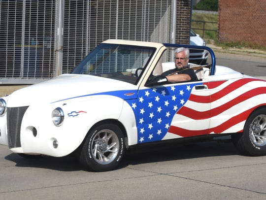 A Chevy custom is draped in the American flag is seen