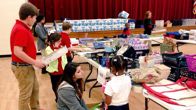 J.I. Barron Sr. Elementary School students shop Thursday for Christmas gifts for their family members at the school's annual Santa Shop fundraiser. Students in Barron's sixth-grade gifted English language arts class and others from Pineville High's Club Kid help them pick out items.