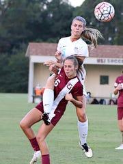 A St. George's player slides under USJ's Anna Jones