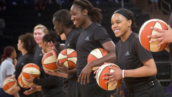 Members of the New York Liberty basketball team await the start of the Wednesday, July 13, game against the Atlanta Dream in New York. The WNBA has fined the New York Liberty, Phoenix Mercury and Indiana Fever and their players for wearing plain black warm-up shirts in the wake of recent shootings by and against police officers.