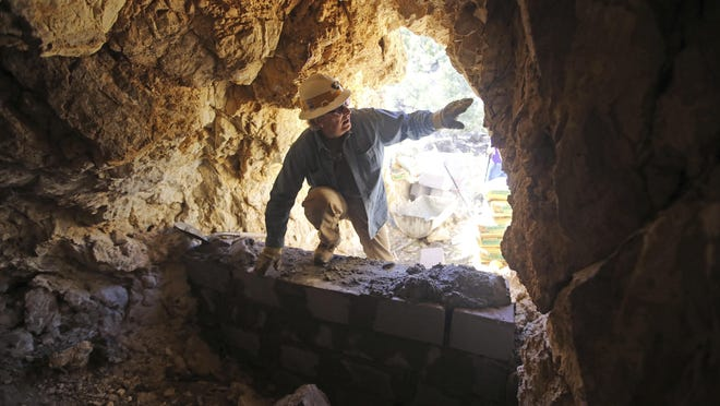In this June 6, 2018, photo, Chris Rohrer, with the Utah Division of Oil, Gas and Mining, climbs in to a cave before its sealed off near Gold Hill, Utah. In Utah alone, the state is trying to seal more than 10,000 open mines with cinderblocks and metal grates after people have died in rock falls and all-terrain-vehicle crashes and from poisonous air over the past three decades.