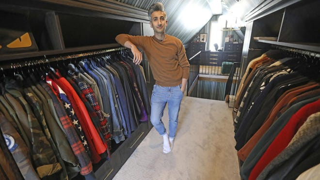 """In this March 15, 2019, photo, Tan France, a cast member on the Netflix series """"Queer Eye,"""" poses among his clothes in his attic. The series touches on some of the country's deepest divides with persistent optimism. The makeover program starring five gay men tackles the contrast between urban and rural, white and black, liberal and conservative."""