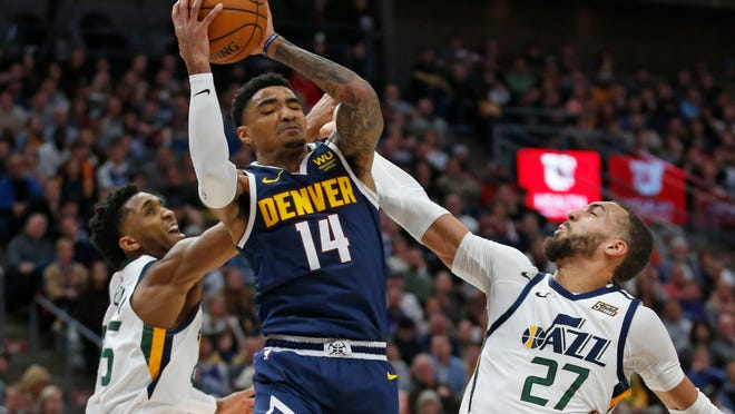 Denver Nuggets guard Gary Harris (14) pulls down a rebound as Utah Jazz's Donovan Mitchell, left, and Rudy Gobert (27) defend during the second half during an NBA basketball game Wednesday, Feb. 5, 2020, in Salt Lake City. (AP Photo/Rick Bowmer)
