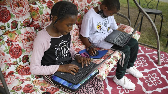 Two siblings, a fourth grader and a third grader, work outside in their yard on laptops provided by their school system for distance learning.