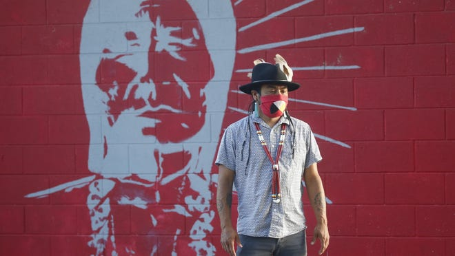 Native American advocate Carl Moore stands in front of a mural of an Indigenous man meant to represent the Braves mascot at Bountiful High School Tuesday, July 28, 2020, in Bountiful, Utah. While advocates have made strides in getting Native American symbols and names changed in sports, they say there's still work to do mainly at the high school level, where mascots like Braves, Indians, Warriors, Chiefs and Redskins persist.