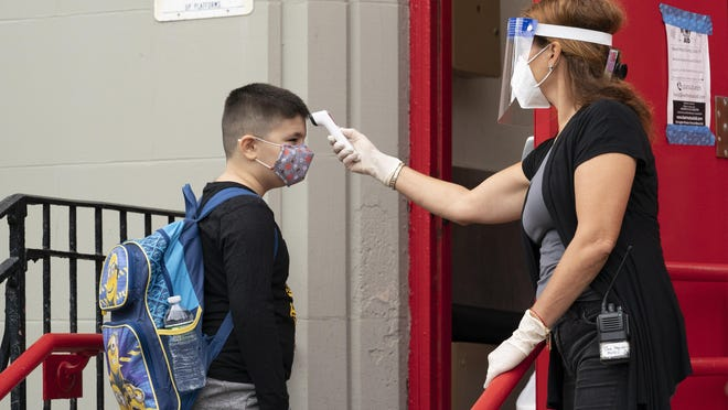 A student has his temperature taken before entering PS 179 elementary school in the Kensington neighborhood, Tuesday, Sept. 29, 2020, in the Brooklyn borough of New York. Hundreds of thousands of elementary school students are heading back to classrooms Tuesday as New York City enters a high-stakes phase of resuming in-person learning during the coronavirus pandemic.