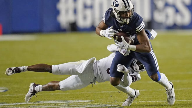 BYU wide receiver Keanu Hill tries to shake loose from Texas State cornerback Jarron Morris after catching a pass Saturday night.