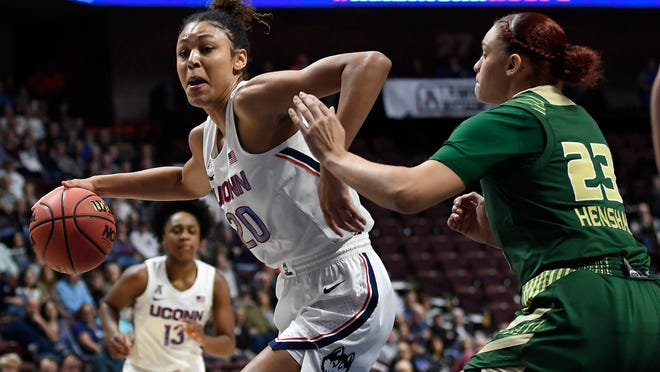 """FILE - Connecticut's Olivia Nelson-Ododa, left, drives around South Florida's Tamara Henshaw during the first half of an NCAA college basketball game in the American Athletic Conference tournament semifinals at Mohegan Sun Arena, Sunday, March 8, 2020, in Uncasville, Conn. UConn officials have discussed creating helmet stickers, warm-up T-shirts and altering athletic uniforms in other ways to show support for the Black Lives Matter movement. """"I believe as athletes that we have this platform, especially here, we have a platform and a voice and we should use it, especially on topics like this that have been going on for hundreds of years,"""" center Olivia Nelson-Ododa said last month. """"And so the ability to speak out about it and advocating for the Black Lives Matter movement is very important to me, and I know for the rest of my team as well."""""""