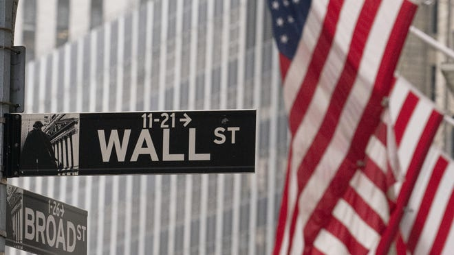 FILE - A street sign for Wall Street is seen outside the New York Stock Exchange, Thursday, Nov. 5, 2020.  One of Wall Street's big fears coming into this month was a contested U.S. presidential election.  President Donald Trump is refusing to concede even though Democrat Joe Biden secured enough electoral votes to win the presidency. Yet the S&P 500 has climbed this month back to the edge of its record high.