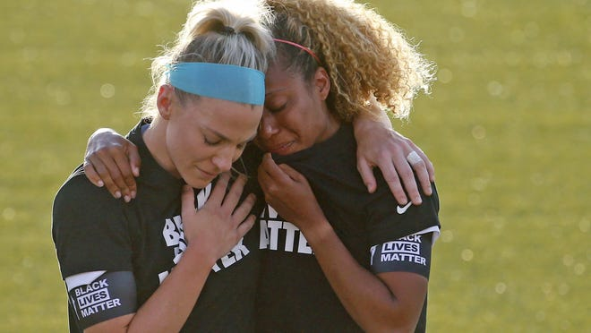 Chicago Red Stars' Julie Ertz, left, holds Casey Short, after players for the Chicago Red Stars kneel during the national anthem Saturday in Herriman, Utah.