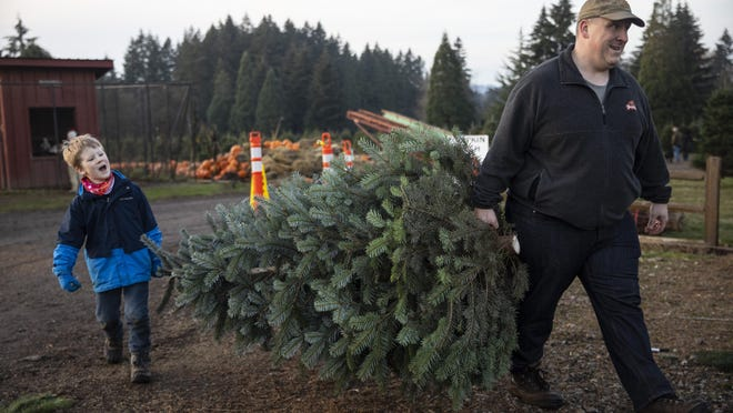 Tim Daley and son Jacob, 9 years, from Tualatin carry their freshly cut Christmas tree at Lee farms on Saturday, Nov. 21, 2020 in Tualatin, Ore. It's early in the season, but both wholesale tree farmers and small cut-your-own lots are reporting strong demand, with many opening well before Thanksgiving.