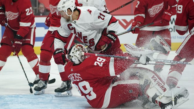 Carolina Hurricanes right wing Nino Niederreiter (21) scores on Detroit Red Wings goaltender Thomas Greiss (29) in the first period of an NHL hockey game Thursday, Jan. 14, 2021, in Detroit.