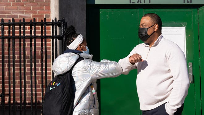 Linsey Johnson, right, a dean at Meyer Levin Middle School, greets a student Thursday in New York.