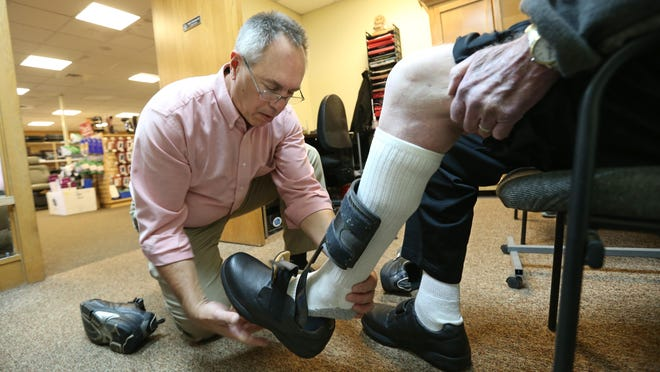 Mark Delmotte, a certified orthotist, helps a customer try on a new pair of orthopedic shoes at Westside Medical Supply in Gates Friday, Nov. 11, 2016.