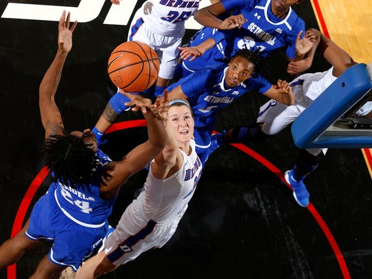 Kelly Campbell (center, in white) goes for a rebound.