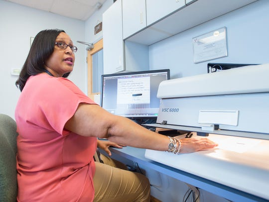 Crime laboratory analyst Kesha White demonstrates how