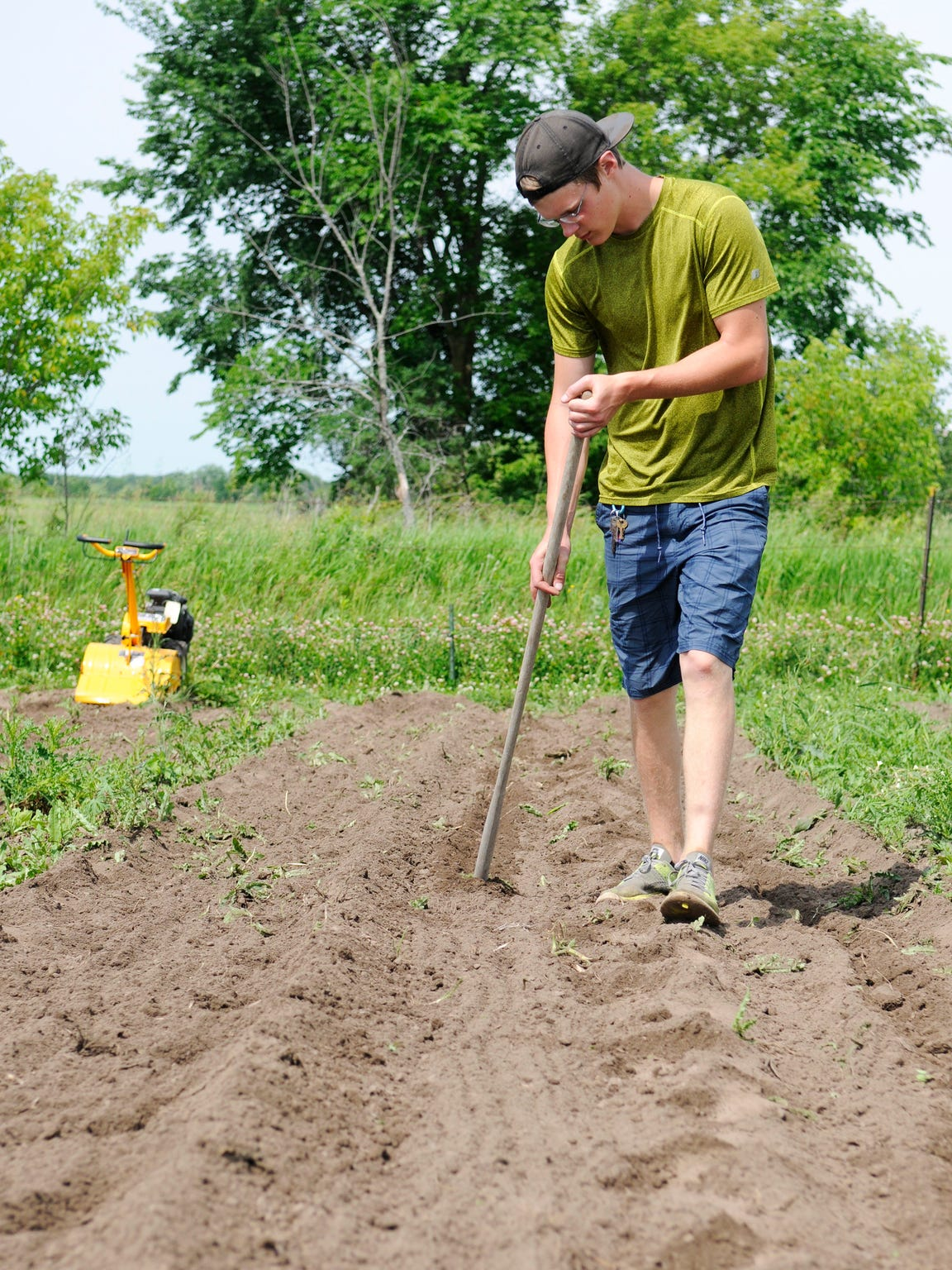 Alex Bertsch prepares to plant watermelon seeds at