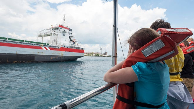 Belle River fifth-grader Kylin Satterly, 10, covers her ears in anticipation of the Wagenborg Beatrix freighter from the Netherlands blowing its horn.