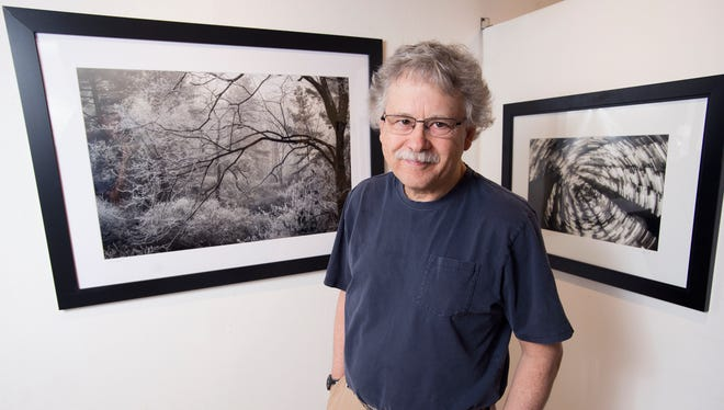 Photographer Chuck Haupt with several of his printed photographs at Cooperative Gallery 213 in downtown Binghamton.