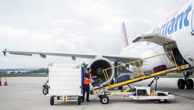 A worker loads bags onto an Allegiant Air jet at Asheville Regional Airport in this file photo.