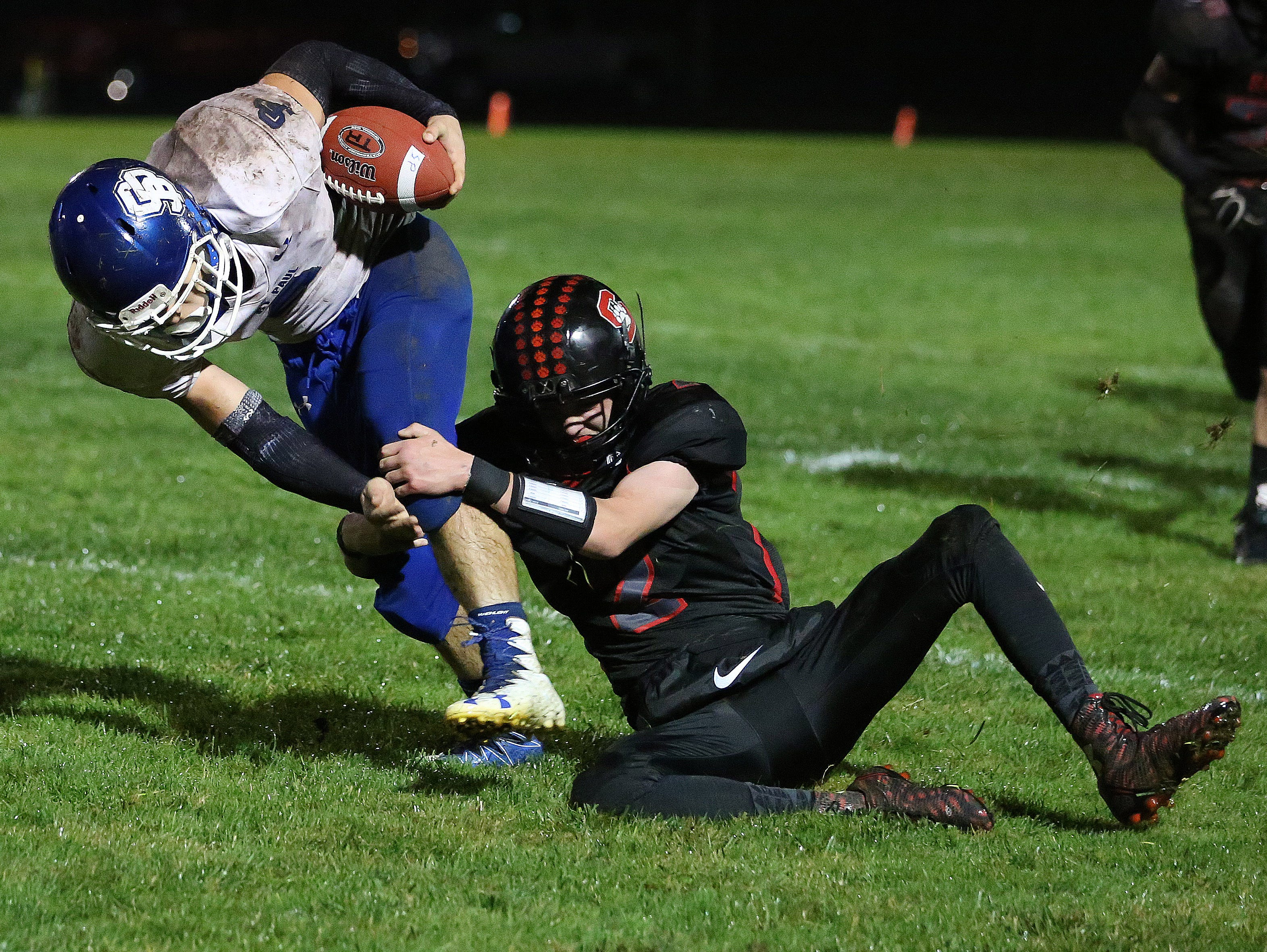 Santiam's Kole Amaral helps take down St. Paul's Fernando Dela Cerda in a Tri-River Conference game on Friday, Oct. 7, 2016, at Santiam High School in Mill City.